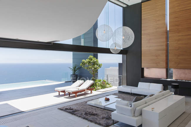 Living room and patio of modern house overlooking ocean — Stock Photo