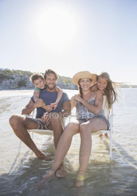 Família sentada em cadeiras em ondas — Fotografia de Stock