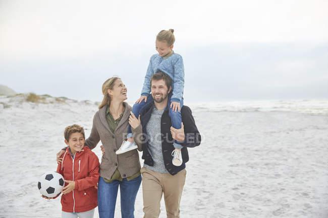 Famiglia con pallone da calcio passeggiando sulla spiaggia invernale — Foto stock
