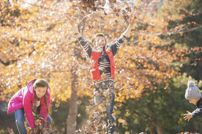 Ragazzi giocosi e ragazza che corrono e saltano in foglie autunnali — Foto stock