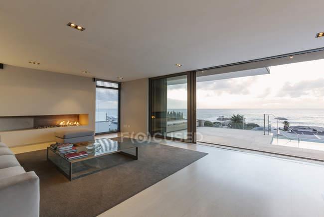 Salone di lusso moderno, minimalista con gas camino e patio porte aperte per patio e vista oceano — Foto stock