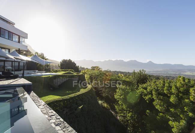 Современный роскошный дом с витриной и бассейном с видом на солнечные горы — стоковое фото