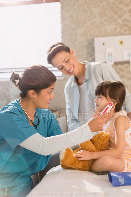 Infermiera femminile che utilizza il termometro digitale nell'orecchio della paziente in camera d'ospedale — Foto stock