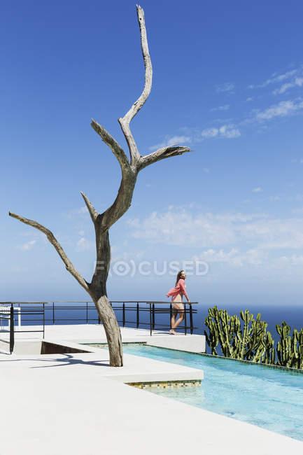 Женщина стоит на балконе у бассейна с видом на океан — стоковое фото