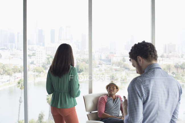 Casual business people in office overlooking city — Stock Photo