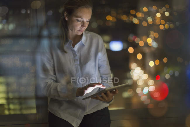 Businesswoman working late at digital tablet in office at night — Stock Photo