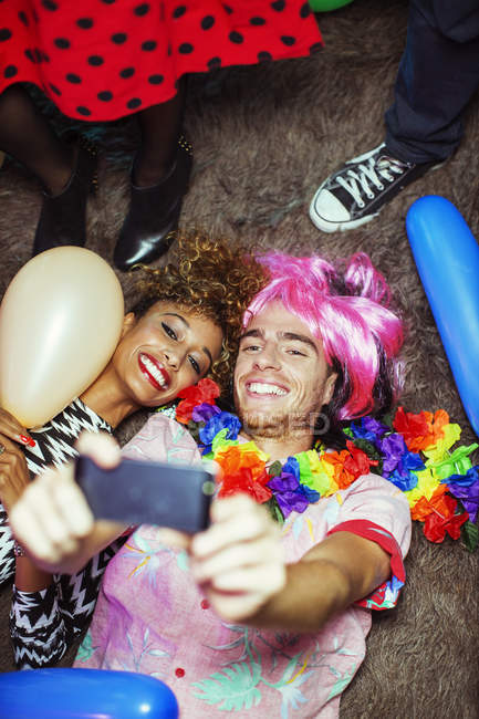 Couple taking self-portraits with smartphone on floor at party — Stock Photo