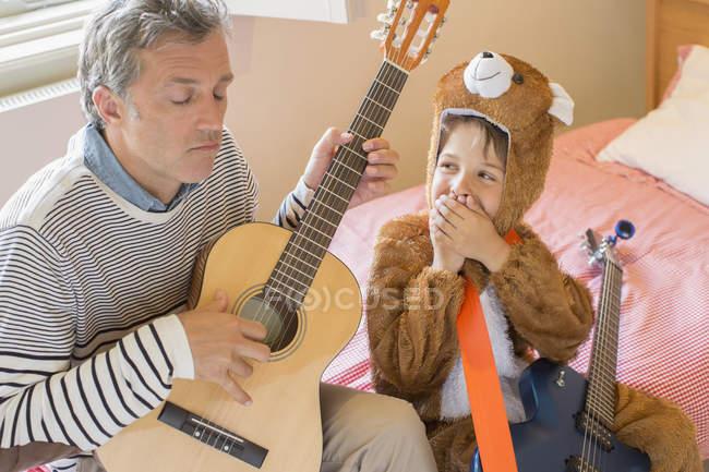 Pai e filho tocando guitarra juntos — Fotografia de Stock