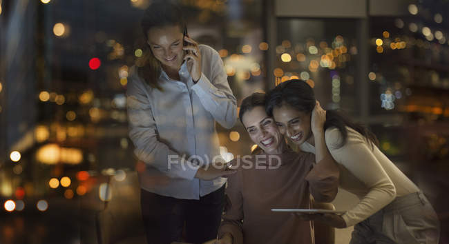 Happy businesswomen celebrating, working late in office at night — Stock Photo