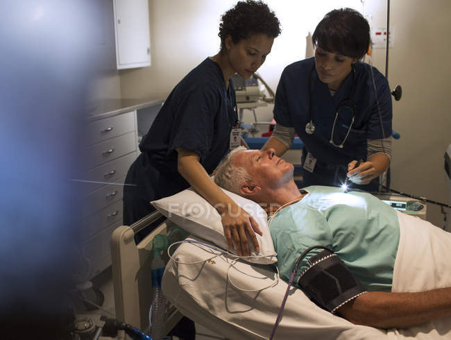 Two doctors attending patient in hospital ward — Stock Photo
