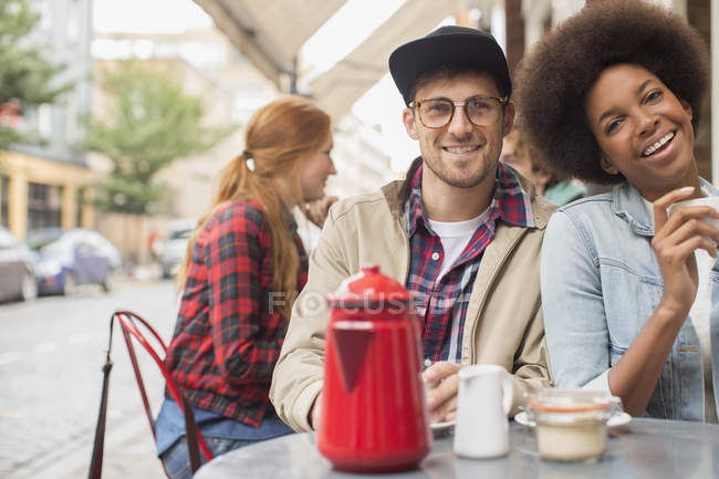 Couple drinking coffee at sidewalk cafe — Stock Photo