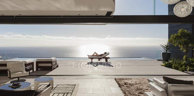 Жінка засмагати на шезлонгу на біля басейну з видом на океан — стокове фото