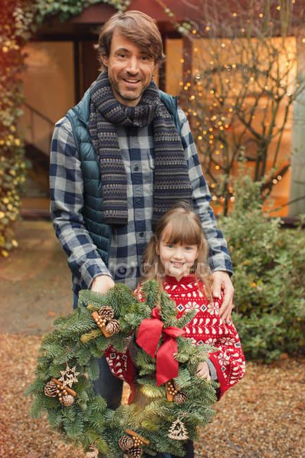 Ritratto padre e figlia sorridenti con ghirlanda natalizia — Foto stock