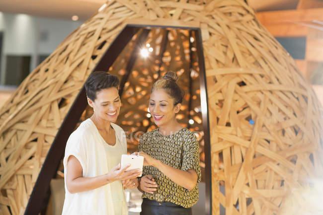 Mujeres de negocios creativas sonrientes usando el teléfono inteligente en el espacio de trabajo creativo tipi - foto de stock