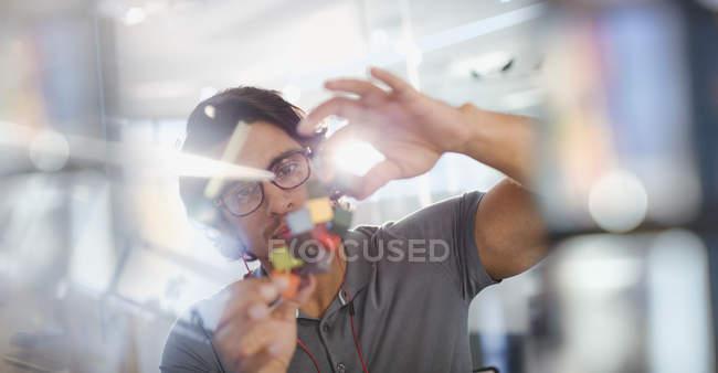 Focado, inovador empreendedor masculino examinando o protótipo — Fotografia de Stock
