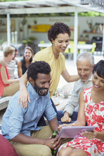 Friends using digital tablet at party — Stock Photo
