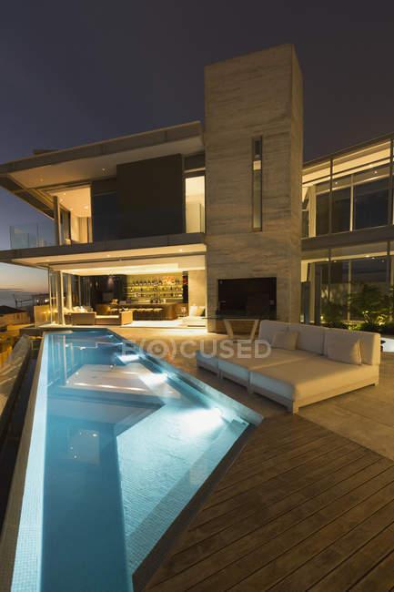Illuminated modern luxury home showcase exterior patio with lap pool — Stock Photo