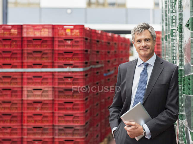 Portrait of confident supervisor with digital tablet in food processing plant — Stock Photo