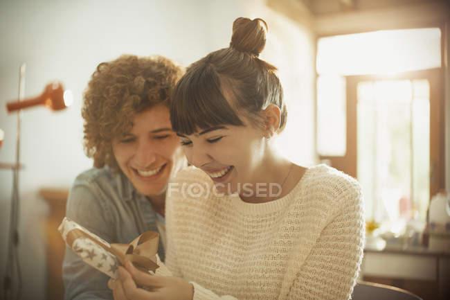 Усміхаючись молода пара відкриття подарунок до дня народження — стокове фото