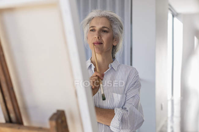 Pensive mature woman painting at easel — Stock Photo