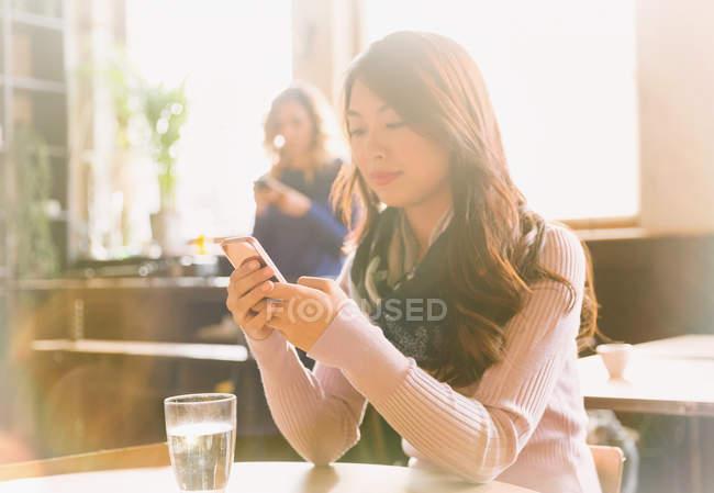 Mulher mensagens de texto com telefone celular na mesa de café — Fotografia de Stock
