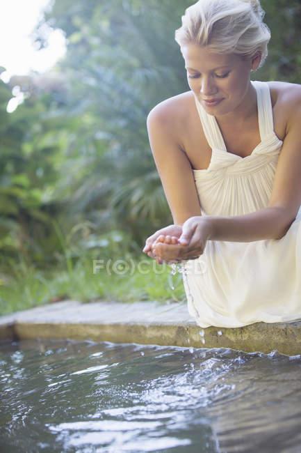 Donna coppettazione piscina acqua in mano — Foto stock
