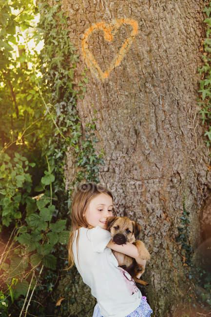 Девушка держит щенка под деревом в форме сердца — стоковое фото