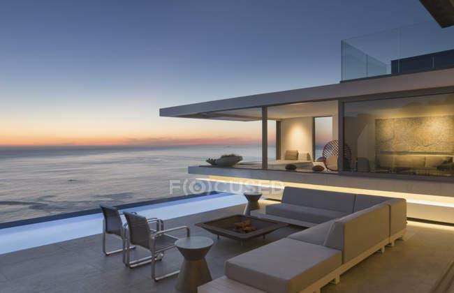 Освітленій сучасні, розкішні будинку Вітрина зовнішніх патіо з диваном і lap басейн з видом на океан в сутінках — стокове фото