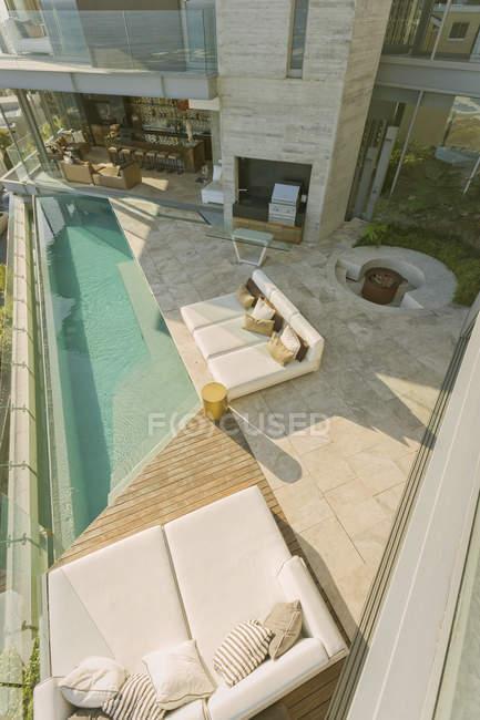 Солнечный современный роскошный витринный дворик с шезлонгами и бассейном — стоковое фото