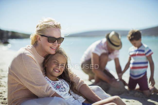Grandmother hugging granddaughter on beach — Stock Photo