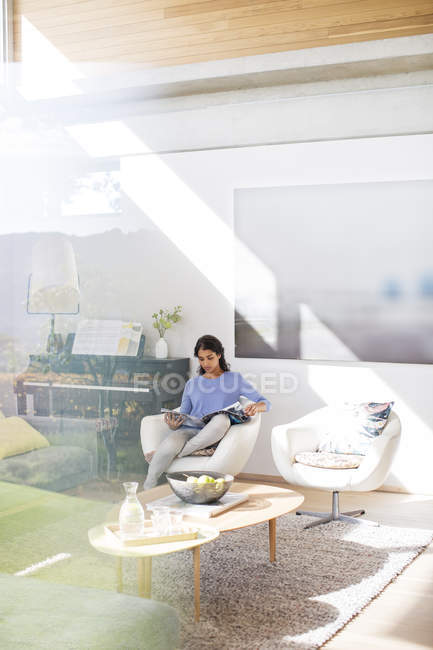 Woman reading magazine in sunny living room — Stock Photo