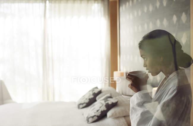 Женщина в Халат, попивая кофе в спальне — стоковое фото