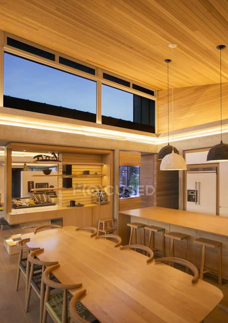 Tecto de madeira iluminado sobre cozinha e mesa de jantar — Fotografia de Stock