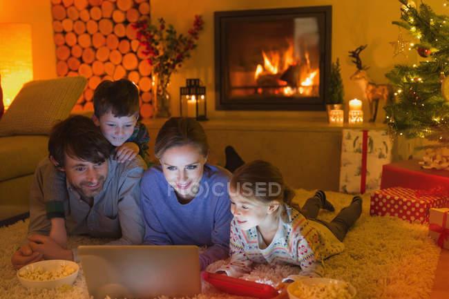 Família comer pipocas e assistir vídeo no laptop na sala de estar ambiente Natal com lareira — Fotografia de Stock