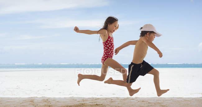 Ragazzo e ragazza fratello e sorella in esecuzione sulla spiaggia tropicale — Foto stock