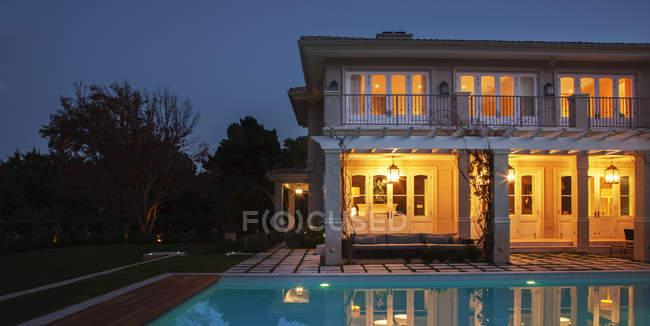 Casa de lujo iluminado con piscina por la noche - foto de stock