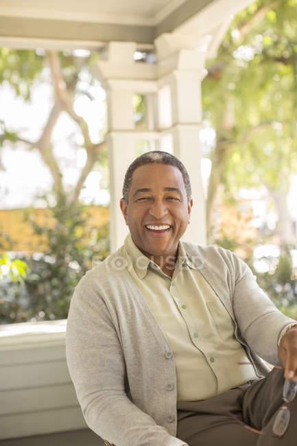 Retrato de hombre mayor riendo en el porche - foto de stock