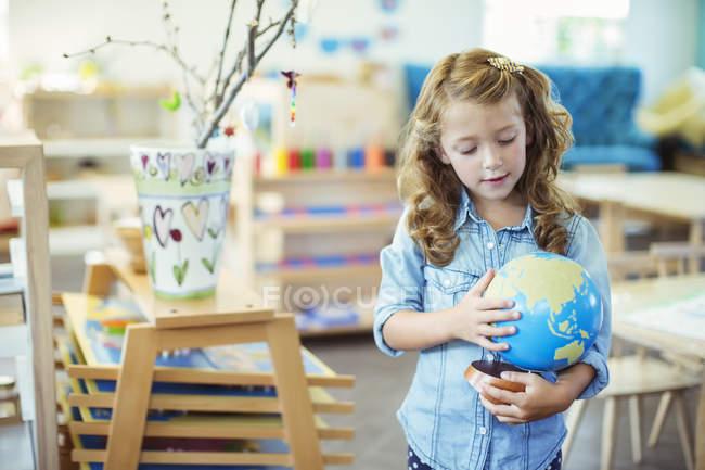 Слідчим глобус студент в класі — стокове фото