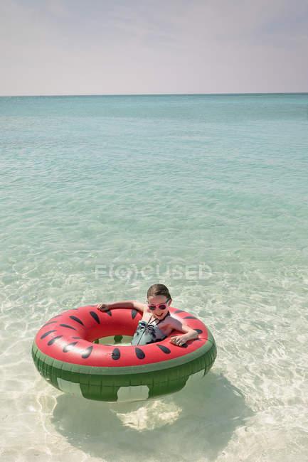 Menina do retrato flutuando no anel inflável de melancia no sol tropical oceano azul — Fotografia de Stock