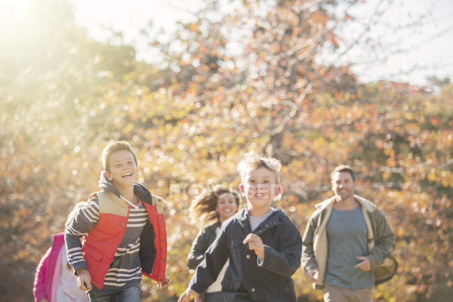 Energetic family running in autumn park — Stock Photo