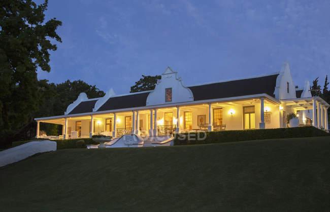 Casa de luxo e varanda iluminada à noite — Fotografia de Stock