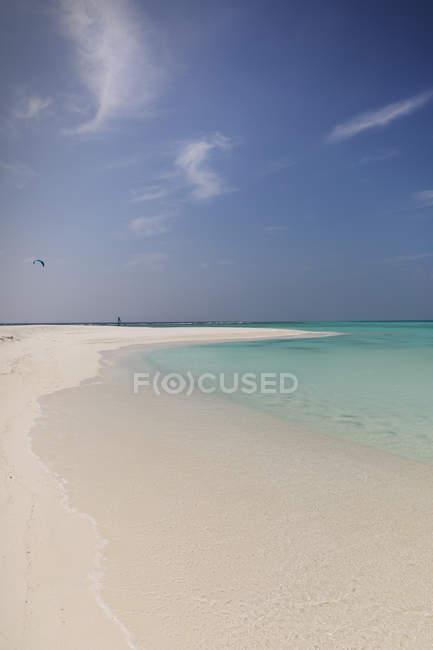 Tranquil tropical ocean beach under sunny blue sky — Stock Photo