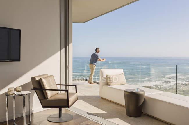Человек наслаждается солнечным видом на океан с роскошного балкона — стоковое фото
