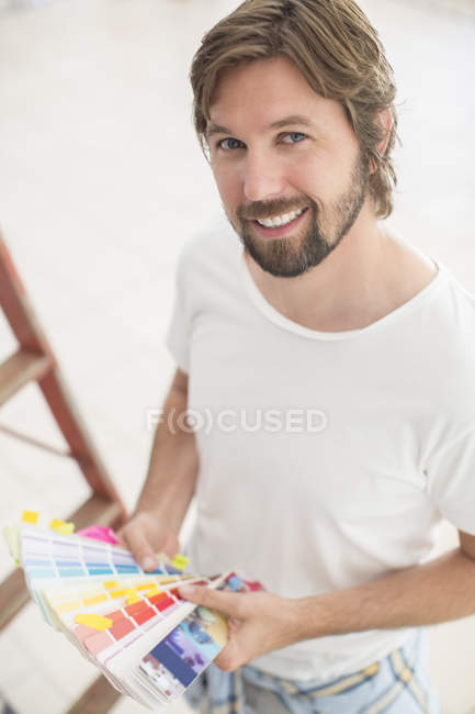 Man looking through color swatches — Stock Photo