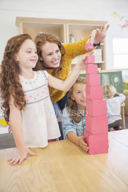 Élèves et enseignants empiler des blocs en salle de classe — Photo de stock
