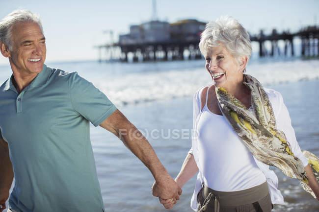 Couple de personnes âgées enthousiaste en cours d'exécution sur la plage — Photo de stock
