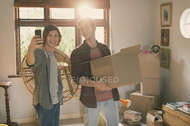 Coinquilini giovani uomini prendendo selfie cartoni per trasloco in appartamento — Foto stock