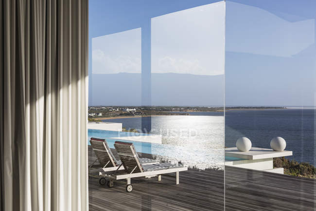 Window view of sunny modern luxury patio with infinity pool and ocean view — Stock Photo