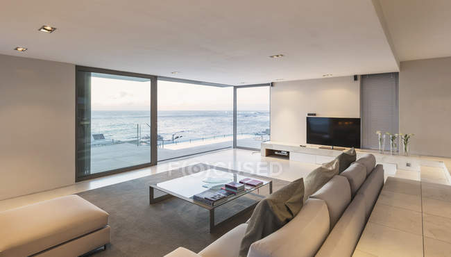 Modern, minimalist luxury living room with patio doors open to ocean view — Stock Photo