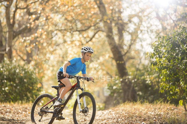 Boy mountain biking on path in woods — Stock Photo